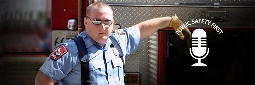 A first responder stands next to an emergency vehicle