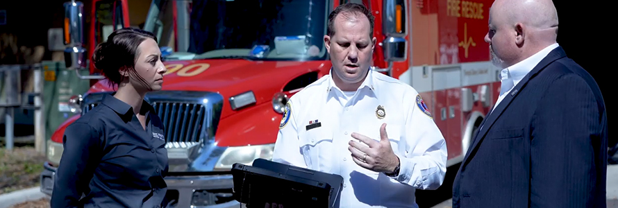 A PSA representative listens to a firefighter holding a mobile computer