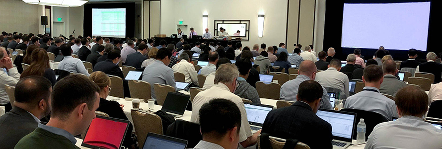 A room full of attendees at the June 2019 3GPP meetings listen and take notes on laptops as a panel of four speakers at the front give a presentation.
