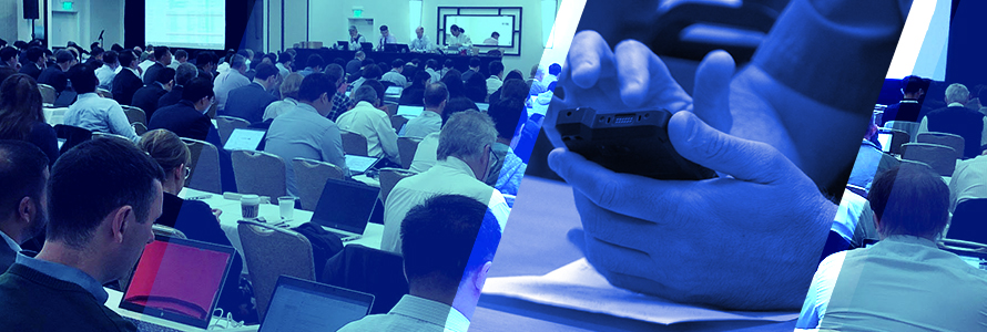 A room full of attendees at the June 2019 3GPP meetings listen and take notes on laptops as a panel of four speakers at the front give a presentation, a police officer holds a FirstNet enabled device