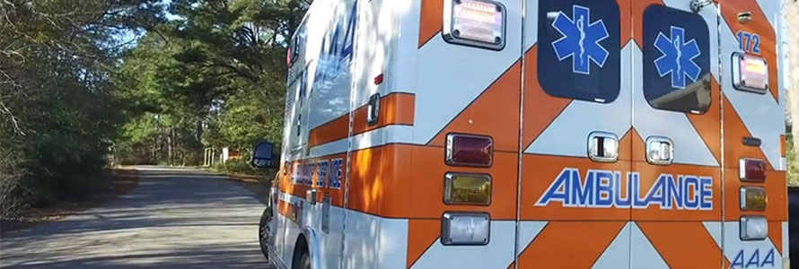 A brightly painted ambulance sits parked on the side of a rural road surrounded by many trees.