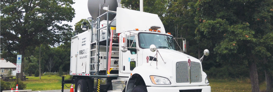 A FirstNet Satellite Cell on Light Truck (SatCOLT) is parked in a rural area and set up to provide a FirstNet LTE connection to support public safety operations.