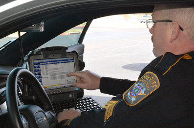 A Brazos County Sheriff's Department officer looks at a screen inside of his patrol car