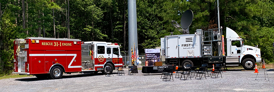 Fire truck and FirstNet Satellite Cell on Light Truck parked in front of a cell tower
