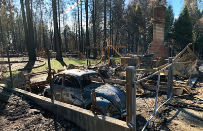A VW bug sits inside the ruins of a burned down house and garage.