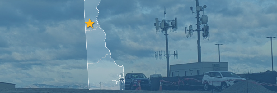 The state of Delaware, with outlined county borders and a star; a cell tower.