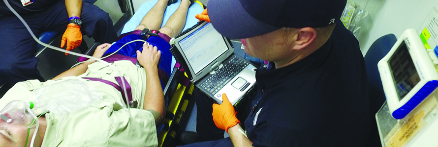 An EMS technician enters patient information into a laptop while riding in the back of an ambulance with a person in a stretcher