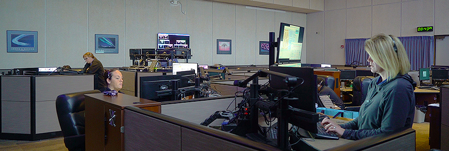 Three 9-1-1 call takers sit at dispatching consoles in a large 9-1-1 call center.