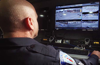 An male officer with the Richmond (Va.) Police Department monitors information n a computer screen.