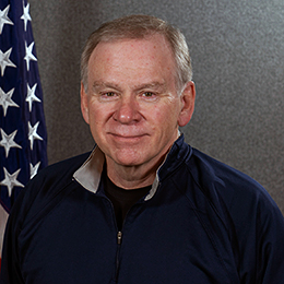 Headshot of John Hunt. He sits in front of an American flag.
