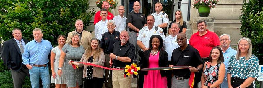 Group of officials and first responders standing in Allegany County, Maryland. Three people are holding a ceremonial ribbon, and one man cuts it with a large pair of scissors.