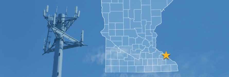The state of Minnesota, with outlined county borders and a star locating the city of Kellogg; a cell tower