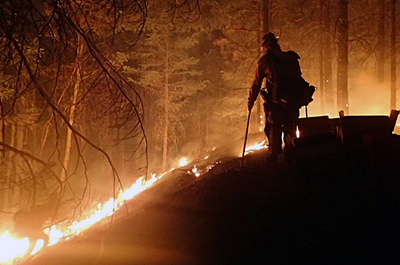A firefighter monitors Sugar Pine/Miles Fire in Oregon at night. Photo credit: U.S. Forest Service – Pacific Northwest Region, July 30, 2018.