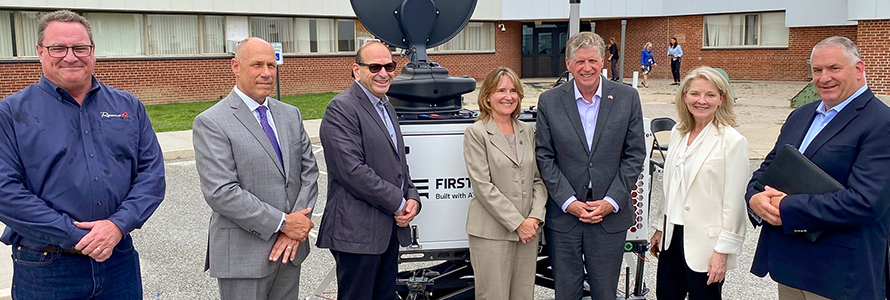 Rhode Island state government, emergency management, FirstNet Authority, and AT&T personnel stand in front of a portable cell site known as a Compact Rapid Deployable.