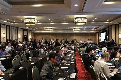Hundreds of people sit in a room during a presentation at the 3GPP plenary meetings June 11-15, 2018 in La Jolla, CA