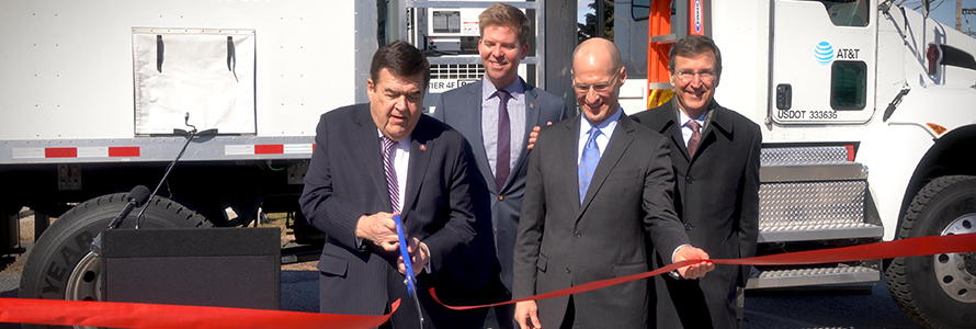 Congressman C.A. Dutch Ruppersberger cuts a red ribbon as FirstNet Authority Acting CEO Ed Parkinson looks on in front of an AT&T SatColt