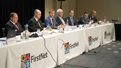 Seven of FirstNet's board members sit at tables during a meeting in front of microphones