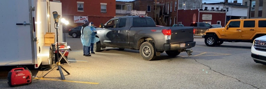 Medical professionals stand by a pickup truck at a COVID-19 testing site.