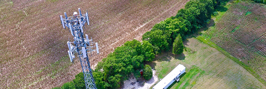 Aerial view of the top of a FirstNet cell site tower with a field and grove of trees in the background.