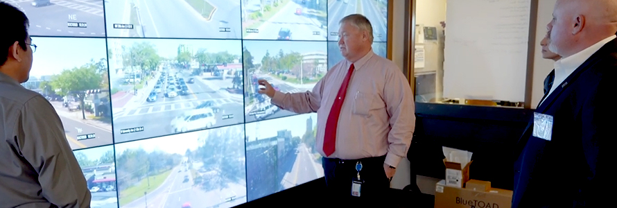 Public works staff from Gainesville, Florida consult several screens showing live stream video from around the city.