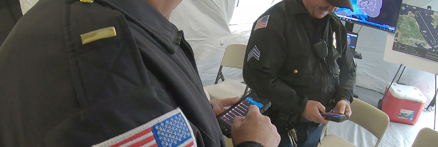 Two officers in uniform look down at FirstNet enabled devices
