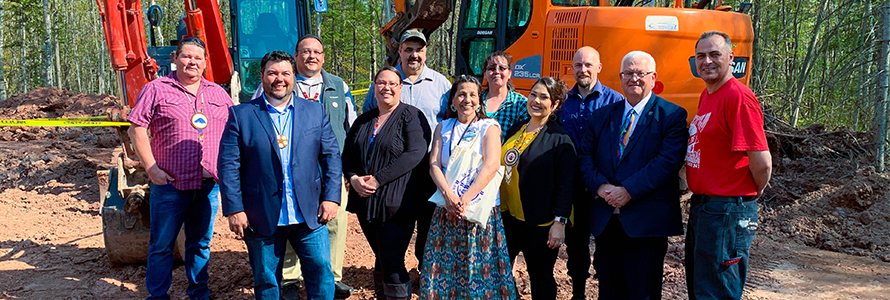 Eleven representatives who broke ground at a cell tower on the Red Cliff reservation stand in front of an excavator.