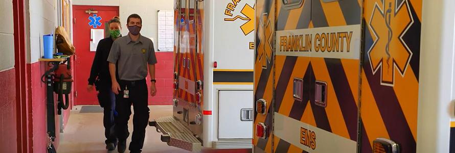 Franklin County EMS personnel walk behind ambulances inside fire station. .