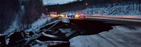 First responder vehicles on a highway destroyed by earthquake