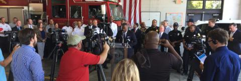 First responders inside a firehouse holding a press conference