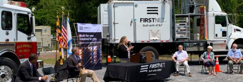 Public safety stakeholders; FirstNet Authority and FirstNet, Built with AT&T, staff; and state politicians sit in front of a fire truck and a deployable satellite truck.