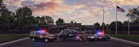 An Oakland County Sheriff's Office SUV, helicopter, motorcycle, and cruiser with emergency lights activated sit outside at sunset