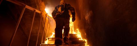 A firefighter ascends a flaming stairwell