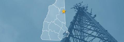 The State of New Hampshire, with outlined county borders and star locating Conway, New Hampshire; a cell tower.