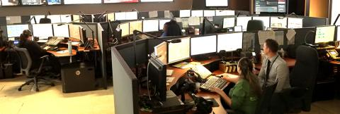 Miami-Dade dispatchers take calls and discuss issues inside of their center surrounded by information on various screens