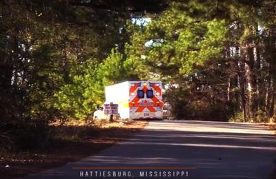 An ambulance drives down a small road on a sunny day.