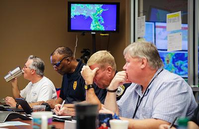 Pictured left to right sitting at a table with displays showing maps behind them: Gainesville (FL) Fire Chief Jeff Lane; Police Chief Tony Jones; Asst. Police Chief Terry Pierce; and Public Works Director Phil Mann.