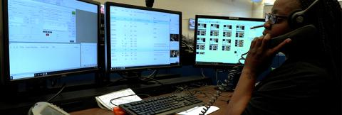 An emergency telecommunicator sits in front of computer monitor taking a call