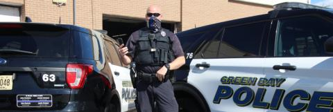 A police officer wearing a mask and a vest stands in front of a Green Bay Police vehicle