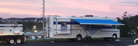 An Indiana County Emergency Management vehicle sits in a parking lot at sunset.