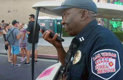 A City of Las Vegas Fire and Rescue uniformed officer speaks into a smartphone. Behind him are music festival attendees.