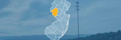 The state of New Jersey, with outlined county borders; a cell tower.