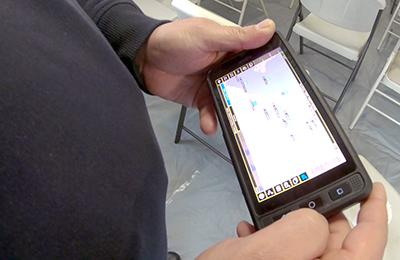 A FirstNet enabled phone held by an officer displaying an app