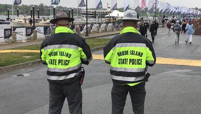 Two officers in Rhode Island State Police jackets look at the crowd at the 2018 Volvo Ocean Racenear the water