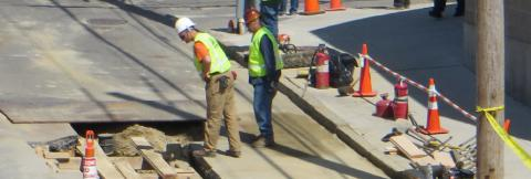 Workers in safety vests and hard hats observe a hole in the street.