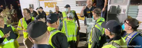 A group of first responders wearing yellow vests and medical masks gather outside an emergency response vehicle preparing to assist after a tornado near Jonesboro, Arkansas