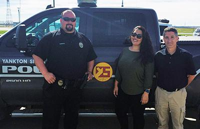 Two men and one woman stand in front of a Yankton Police truck. One of the men wears a police uniform.