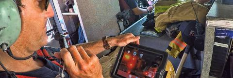 A firefigther riding in a helicopter speaks into a headset while looking down at a tablet with information