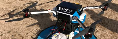 A blue and white flying COW with the AT&T FirstNet logo on it's top sits on the ground ready to launch