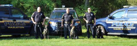 Three police officers standing in front of three Hazelton Police Department vehicles, each holding the leash of a German shepherd dog.