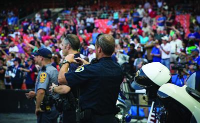 Three police officers using devices stand in front of a large group of people in a stadium